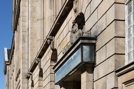 Bildhafte Fassadengestaltung über den Haupteingang aus gesehen