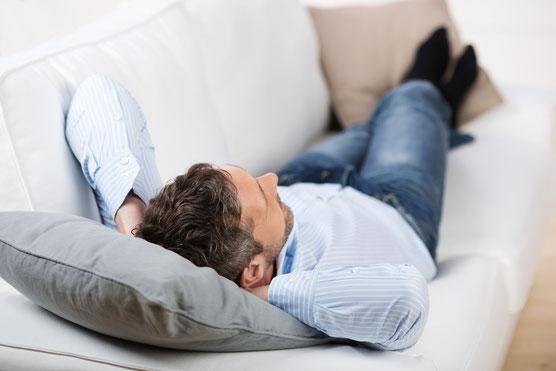 Mann liegt auf dem Sofa und faulenzt