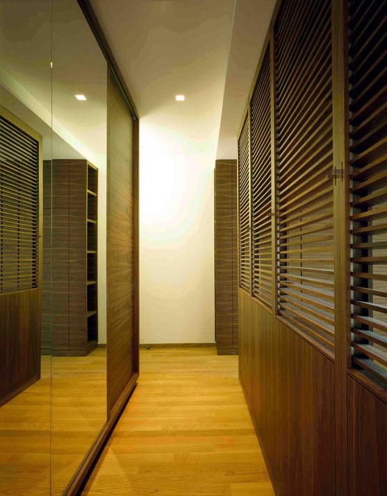 Schrankraum aus Holzwerkstoffplatten furniert und Nussholz massiv, Schiebetüren verspiegelt. Zum Schlafbereich mit verstellbaren Holzlamellen aus Nussholz abdunkelbar - Foto © G. Zugmann