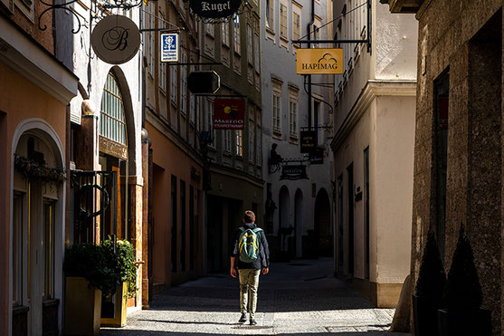 A young man marches a shady alley in Salzburg