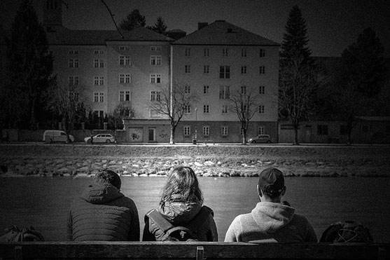 Black and white photo. 3 young men sitting on the banks of the river Salzach