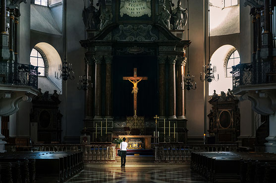 A young woman stands in front of the cross of Christ in the Salzburg Cathedral