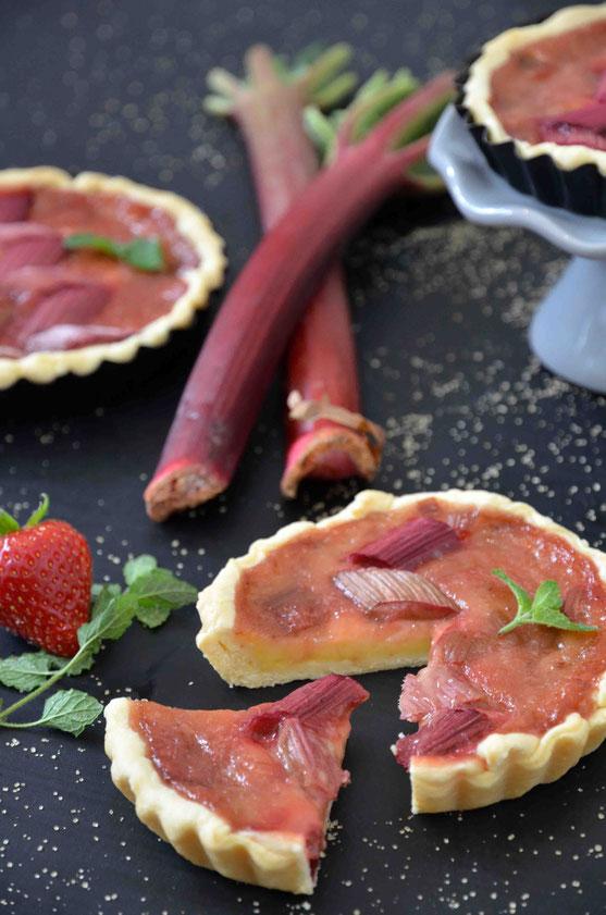 Angeschnittene Rhabarber-Tarte, gefüllt mit Vanillepudding und getoppt mit Erdbeer-Rhabarber-Kompott. (vegan)