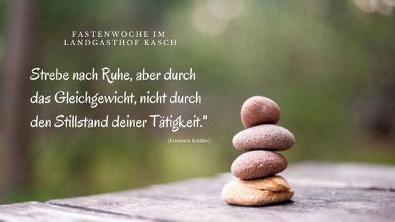 """Bild mit aufgestapelten Steinen und Text """"Strebe nach Ruhe, aber durch das Gleichgewicht, nicht durch den Stillstand deiner Tätigkeit"""""""