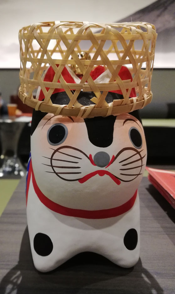 Inu hariko con cesta de bambú en la cabeza