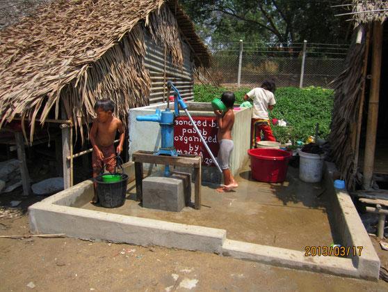 Arrivée d'un nouveau puits d'eau potable financé par PASDB (ce qui est indiqué sur le puits en blanc sur fond rouge) dans le faubourg de Hlaing Thayar (Yangon). Environ 900 personnes en bénéficient.