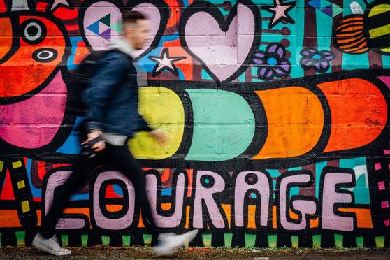 Mann geht einer Wand entlang. Dort buntes Graffiti mit der Aufschrift: Courage,