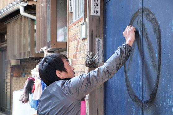 玄関の戸にまるはちを描く男性