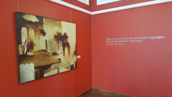 """Ölgemälde in Sand- und Erdfarben, daneben Text: """"Man muss sich mit dem Entdecken begnügen und auf das Erklären verzichten (Georges Braque)"""""""