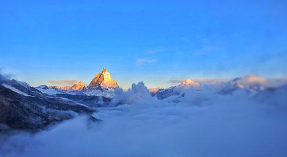 Sonne auf Gipfel über den Wolken, Burnout- Prophylaxe bei Traumatherapie oder Coaching