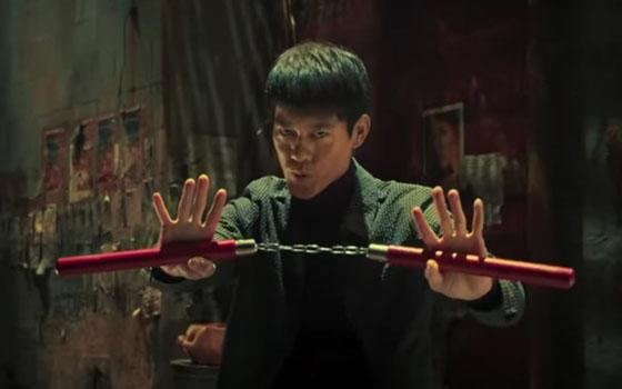 Kwok-Kwan Chan spielt die Rolle des Bruce Lee und hält das Nun-Chaku in die Kamera.
