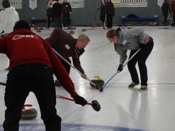 Curling in Toronto: Wischen ist wichtig. Dadurch kann man dafür sorgen, dass es der eigene Stein noch ins Haus schafft / dass ein gegnerischer Stein über das Ziel hinaus schiesst. Auf Letzteres spekuliert hier der Spieler in Rot.