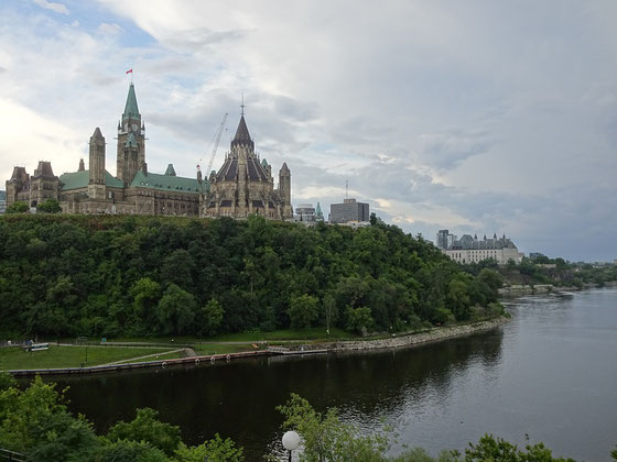 Urlaub in Ottawa: Blick auf den Parliament Hill mit dem Palament, dem Peace Tower und der Bibliothek. Unten fliesst der Ottawa River, und am linken Bildrand geht es zu den Schleusen des Rideau-Kanals.