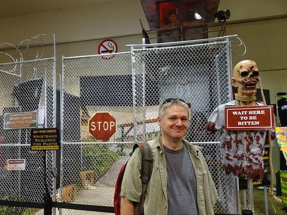 """Bühnenbild von der FanExpo mit Wachturm hinter  einem Gitterzaun. Vor dem Zaun steht ein Skelett mit einem Schild """"Wait here to be bitten""""."""