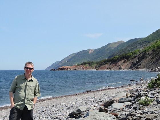 Geocacher am Cabot Trail: Im Hintergrund erkennt man die Strasse, die sich über Kilometer am Meer entlang schlängelt, bevor sie landeinwärts in den Cape Breton Highlands National Park abbiegt.