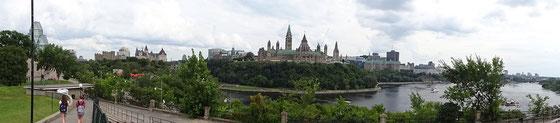 Panorama-Bild aus Ottawa: Links erkennt man die Glaskuppel der Nationalgalerie, etwas weiter rechts das Hotel Chateau Laurier, in der Mitte erhebt sich der Parliament Hill aus dem Ottawa River, und ringsherum viel Grün dank der unzähligen Parks.