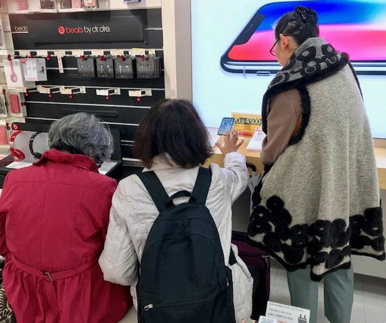 ☆バスで用賀駅まで移動。auショップ到着16:20頃。購入ご希望は写真左側の赤い服装のご婦人です。後学のために生田さん・中島さん・佐藤さんともども同伴。ご希望はiPhone 8 Plus。ただいま物色中。