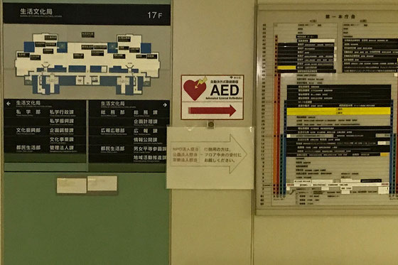 ☆都庁生活文化部。NPO法人の届出窓口の案内板が「AED」の矢印の下に張り紙。