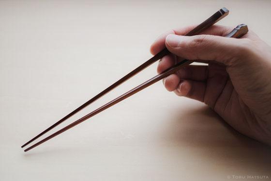煤竹箸を手にしたイメージ。竹工芸家 初田徹