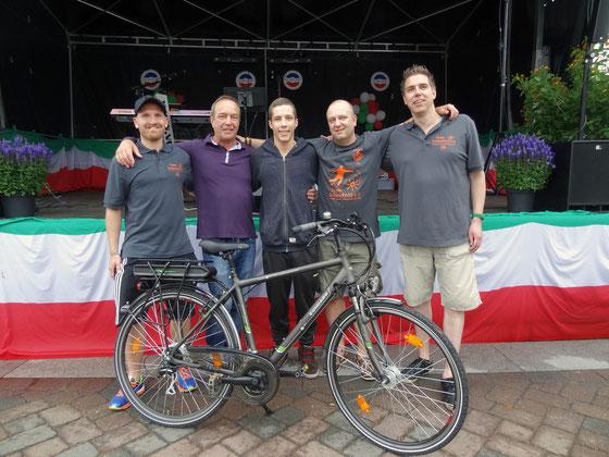 Lars (Mitte) nimmt sein E-Bike in Empfang
