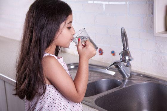 Mädchen trinkt Wasser aus dem Wasserhahn.