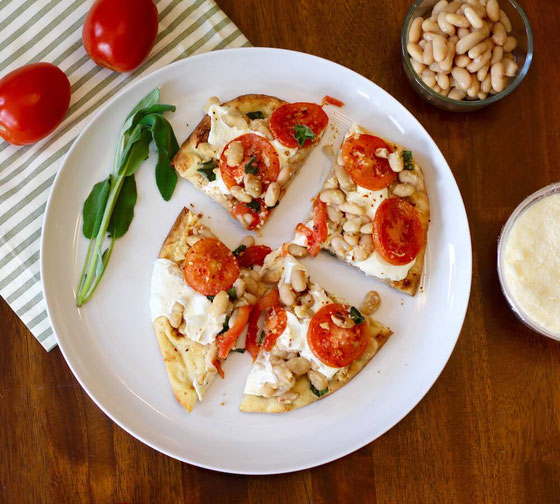 Looking for healthy recipes? This Tomato and White Bean Naan Pizza is vegetarian and can be eaten for breakfast, lunch, or dinner! Just pop it in the oven.