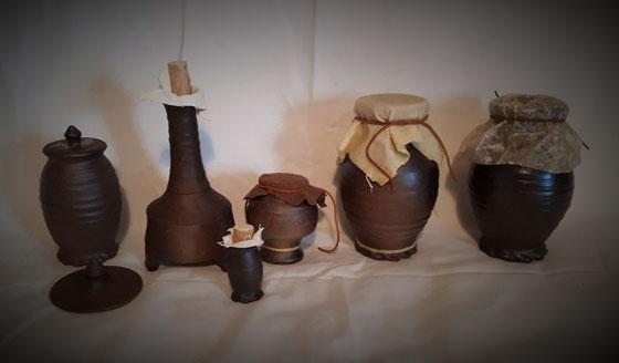 Gefäße zur Lagerung mit verschiedenen Verschlusssytemen. Von Links nach Rechts: Einfacher Deckel aus Keramik, Holzkorken mit Leinentuch, Leder, Wachstuch (Leinen in Bienenwachs getränkt) und Schweineblase.