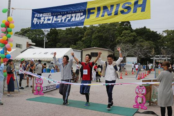 第一コンサルタンツ高知大学原研究室連合Bチームの尾﨑(スイム)、石川(バイク、高知大)、吉田(ラン)の選手がゴール。2時間28分で第6位。