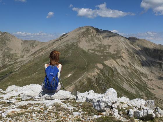 Une femme assise au sommet d'une montagne en été, regarde l'horizon dégagé et calme devant elle