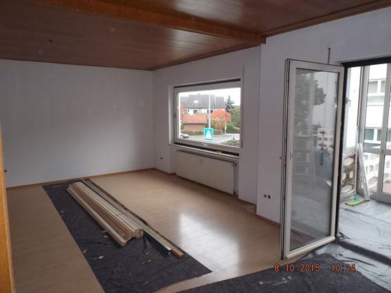 weißer Raum mit Laminatboden und Holzdecke
