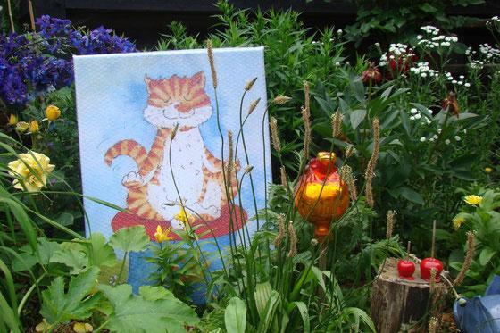 Das Bild eines Cartoons einer roten Katze in Yoga-Haltung ist dekorativ im Garten platziert.