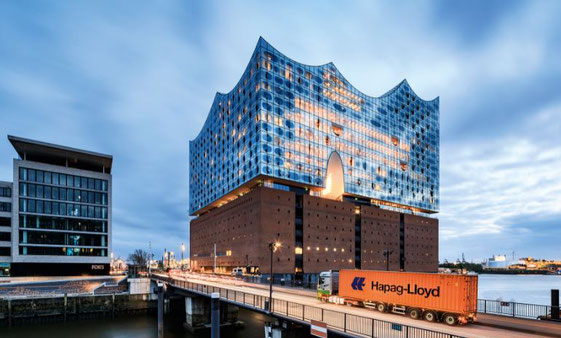 On its way to the harbor, this Hapag-Lloyd container passes Hamburg's new landmark, the Elbe Philharmonic Hall