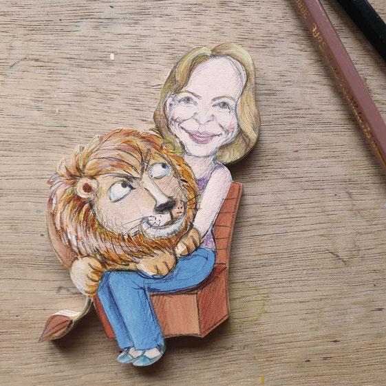 Ein Löwe sitzt auf dem Schoß einer jungen Frau. In der DDR wurden im Tierpark Fotos mit Löwenbabys und Kindern gemacht. Dies ist eine Karikatur dazu.