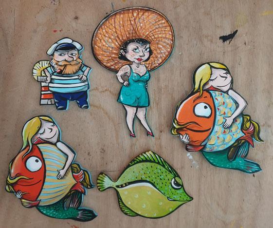 Ein Seemann vor einem kleinen Leuchtturm, eine kleine Frau mit einem riesigen Sonnenhut, die kleine Meerjungfrau mit einem großen Fisch im Arm. Kühlschrankmagnete der besonders feinen Art!
