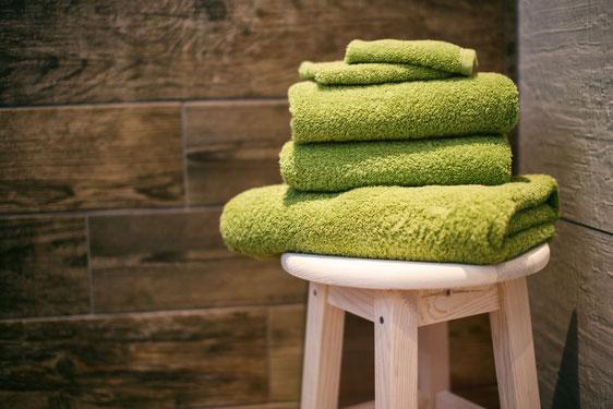 Auf einem hellen Holzhocker liegen vier grüne Handtücher gefaltet aufeinander.