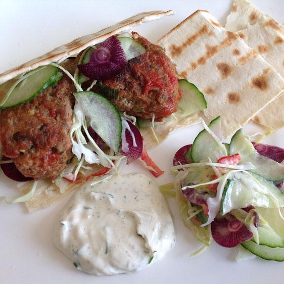 Lamsburgers gevuld met Peyniri, geserveerd met platbrood, salade en gekruide yoghurt.