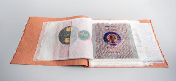 """Verschiedene gedruckte Motive auf Einwickelpapiere von Orangen, Mandarinen, Clementienen und Zitronen. Daraus ein Künstlerbuch """"Orangenhaut"""" erstellt."""