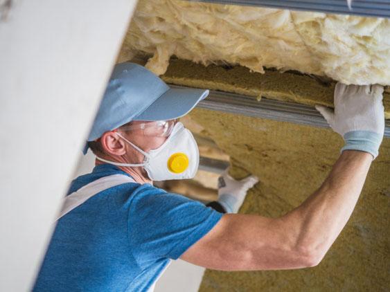 Ein Mitarbeiter der Omega-Spezialbau GmbH beim dämmen einer Kellerdecke