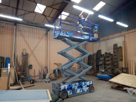 Thierry Besançon entrain d'installer un éclairage LED au plafond dans un atelier professionnel