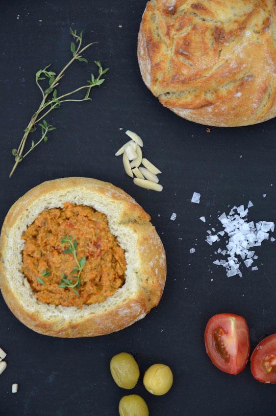 Veganer Antipasti-Aufstrich im Brötchen serviert - eine ausgefallenere Alternative zu vielen im Supermarkt erhältlichen veganen Aufstriche.