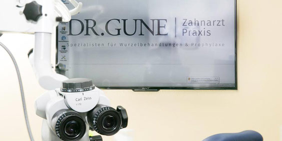 Zahnarztpraxis Dr.Gune in Dallgow-Döberitz - Das Dr.Gune Zahnarzt Logo auf einem Bildschirm von einem ZEISS Operationsmikroskope