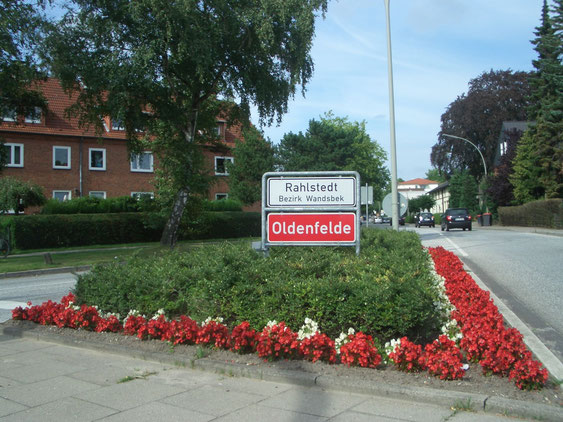 Verkehrsinsel am Alten Zollweg mit rotem Ortsteilschild