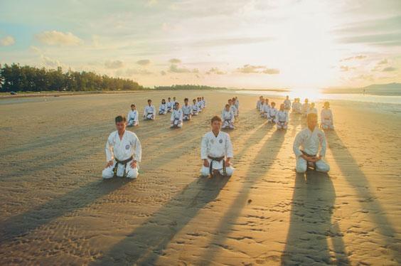 Karateka im Seiza am Strand bei Sonnenaufgang.