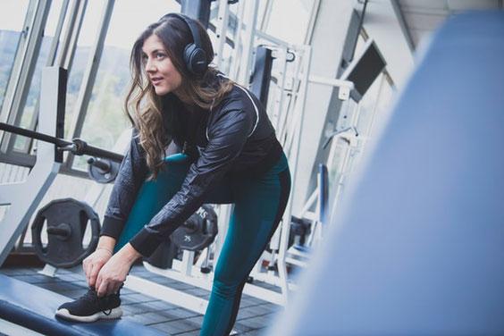 Eine Frau im Fitnesstudio. Sie hat ihren rechten Fuß auf einer Kiste aufgestellt, um sich den Schuh zuzubinden. Sie bereitet sich auf das Training vor und trägt Kopfhörer, um Musik zu hören.