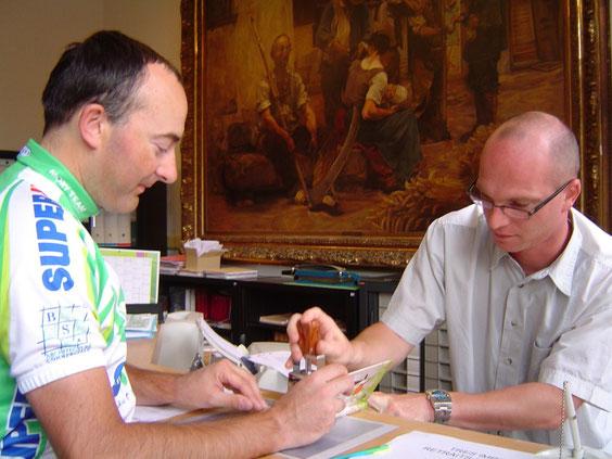 Fabrice fait tamponner son carnet de route à la mairie de Saint-Christophe-sur-le-Nais