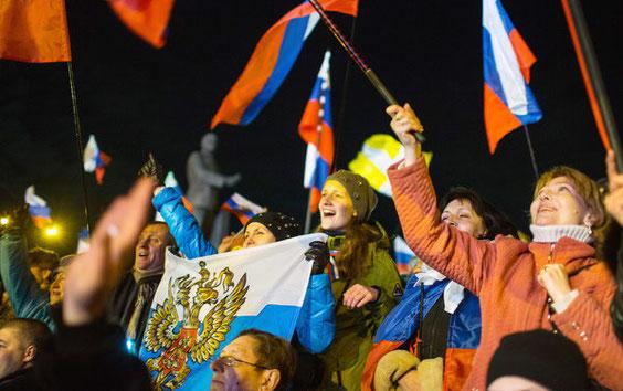 Menschen jubeln nach dem Ende des Referendums auf dem Lenin-Platz in Simferopol auf der Krim-Halbinsel in der Ukraine. Am Sonntag haben mehr als 1,8 Millionen Krim-Bewohner in einem Referendum über den Anschluss an Russland abgestimmt. Foto: dpa