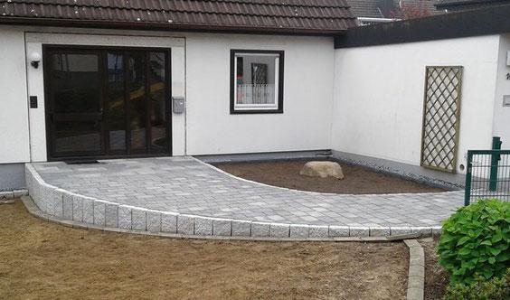 Korfmacher Gartendesign: barrierefreier Eingangsweg mit stark reduziertem Gefälle und pflegeleichten Beeten. Kreis Herford, NRW.
