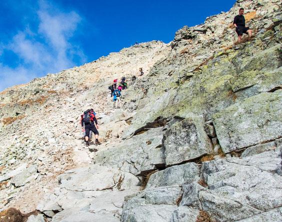 Die letzten Meter hinauf zum Rysy Gipfel. Auf Steinschlag ist zu achten, da hier viele ungeübte Touristen unterwegs sind, die in erster Linie auf sich selbst achten müssen, anstatt auf andere.