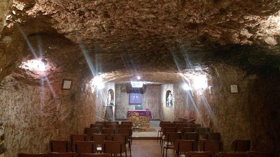 église sous terraine avec plafond bas. c'est en fait une galerie avec un petit autel et des chaises en rang. Il y a l'électricité pour l'éclairage