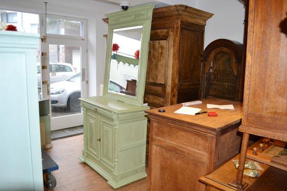 man sieht eine Kommode mit Spiegel im Ladenlokal von Nouvelle-Antique. Die Kommode wurde mit Kreidefarbe gestrichen, der grüne Farbton wurde selbst gemischt.